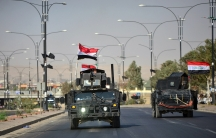 Iraqi security forces advance in military vehicles in Kirkuk on Oct. 16, 2017.