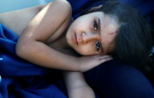 Syrian refugee girl rests inside the Spanish rescue vessel Astral after being rescued by the Spanish NGO Proactiva off the Libyan coast in the Mediterranean Sea.