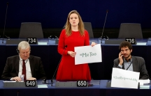 """European Parliament member Terry Reintke (C) holds a placard with the hashtag """"MeToo"""" during a debate"""