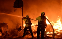 Firefighters battle flames from a Santa Ana wind-driven brush fire called the Thomas Fire in Santa Paula.