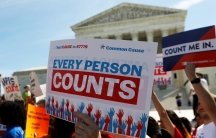 """Protesters stand outside court with sign that reads """"Every person counts"""""""