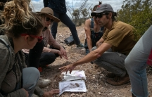 A man crouches in the dirt surrounded by others as they review a few maps.