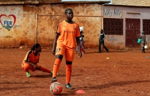 Gaelle Dule Asheri is shown standing with one foot on a soccer ball and wearing an orange uniform.