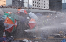 A group of protesters are shown with their umbrellas pointed down to protect themselves from water being shot across the frame of the photograph.