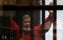 Mohammed Morsi is shown behind bars with his hands raised in the air.