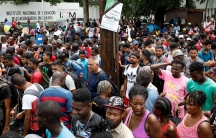 """A large group of people are show standing outside of a white-walled building with the words """"Instituto Nacional de Migracion"""" written on it."""