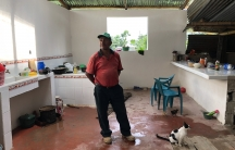 A man stands inside a newly built house in Guatemala built with remittance money from his son, who lives and works in the US.