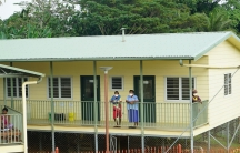 People stand with face masks on the verandah of a yellow hospital building.