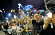 A crowd of activists holds candles in Hong Kong at night.