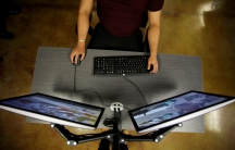 A man sits in front of two computer monitors.