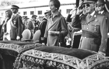 Dictator Francisco Franco stands in military apparel next to his wife at an event.