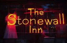 """A neon sign saying """"The Stonewall Inn"""" shines out a window."""