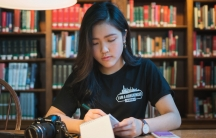 A young woman writing on a notepad