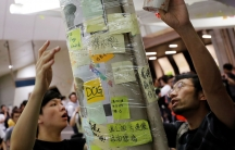 """Two people wrap tape around a column covered in post-it notes to protect the """"Lennon Wall"""""""