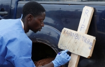 A man in medical scrubs writes onto a wooden cross