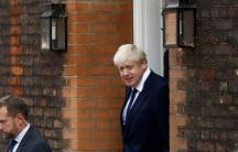 Boris Johnson is shown walking through a brick doorway wearing a blue suit.