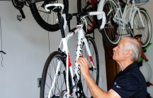 Retired engineer Robert Ozarski invented a device to easily raise and lower bikes from a ceiling. He invested $250,000 out of his retirement savings to start his company, Kradl, but isn't sure about the future of his startup due to the US-China trade war.