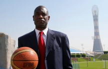 Congolese man in blue suit holds a basketball