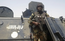 A solider with a gun stands on an armored vehicle.