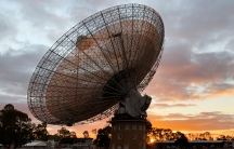 A radio telescope dish at sunset.