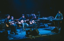 Musicians sit on a stage in blue lighting