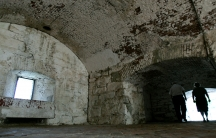 A couple is backlit against a stark stone fort interior.