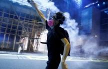 A protester throws a tear gas cartridge against a dark, blue background