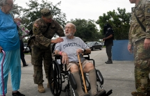 A man in a wheelchair is evacuated during a storm