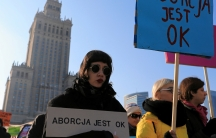 """woman wearing sunglasses holds sign that says """"abortion is ok"""""""