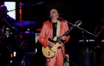 A man in a red suit plays the guitar