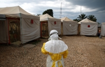 A health worker wearing Ebola protection gear walks next to tents.