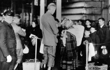 A black and white photo of people going through immigration queues