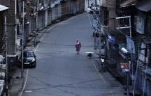 AKashmiri woman walks on a deserted road in Srinagar.