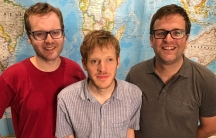 A group of three men are photographed against a world map