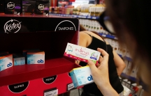 A woman takes tampon boxes out of a supermarket shelf in Buenos Aires January 16, 2015.