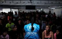 A member ofUnitedNations High Commissioner forRefugees(UNHCR) talks with Venezuelans as they queue in line to receive a vaccine after showing their passports or identity cards at the Pacaraima border control, Roraima state, Brazil, on Aug.8, 2018.