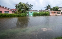 A row of houses are shown from across a flooded street with water up to the front porch of one of the houses.