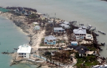 An aerial view of damaged homes, trees and extra debris surrounded by water in the Bahamas.