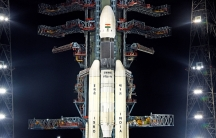 A large, white rocket sits on a launchpad at night time.