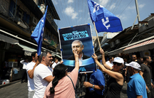 A supporter of the Israeli Likud party kisses an election campaign poster depicting Israel Prime minister Benjamin Netanyahu at the market in Jerusalem.