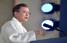 A man wearing a white robe delivers a speech and uses his hand to emphasize a point