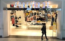 A woman walks in front of the store Forever 21.