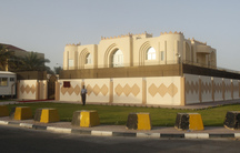 A picture of a tan building with barriers