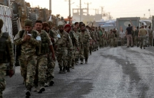 Turkey-backed Syrian rebel fighters walk together in the border town of Akcakale in Sanliurfa province, Turkey, on Oct. 11, 2019.