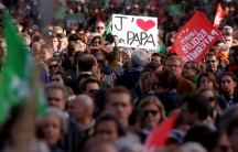 """A crowd of people carry flags. One holds a sign that says """"J'[HEART] Papa."""