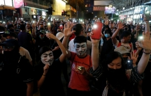 Demonstrators wearing masks hold their cell phones, with the flashlights on, over their heads as they are crowded together in a street