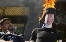 A man stands next to a mannequin with a burning hat.
