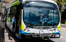 The front of an electric bus is shown with green, blue and white stripes.