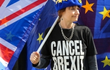 """An anti-Brexit demonstrator is seen wearing an EU flag cap and a t-shirt with """"Cancel Brexit"""" protesting outside the Houses of Parliament."""