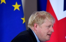Britain's Prime Minister Boris Johnson is shown walking past the EU and UK flags.